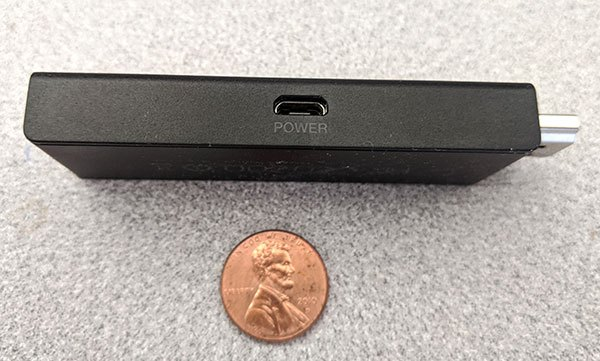 Amazon Fire TV Stick side showing micro USB power input and a penny