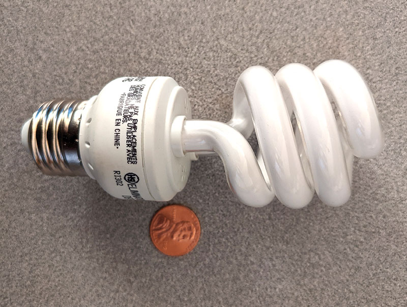 photo of the other side of the second CFL bulb laying on a table with a penny for scale
